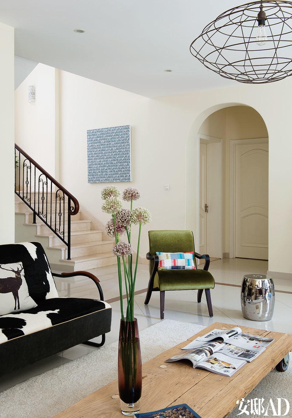 客厅的另一侧,绿色丝绒复古扶手椅来自上海的Ting家居店,上面摆着Trine自己设计的靠垫,靠楼梯的墙上挂着陈灵刚的艺术作品。