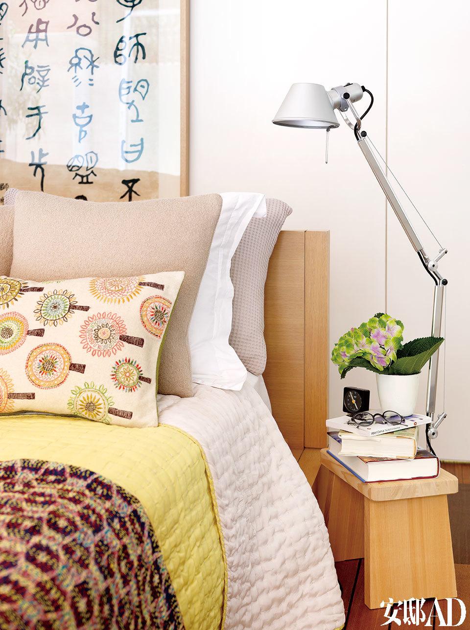 夫妇俩的卧室是一个令人舒缓的空间,一幅晚清时期谢增的书法添色不少。 卧室,日式小凳子来自无印良品,做床头柜恰到好处,刚好够放一摞书,床头灯来自Artemide。