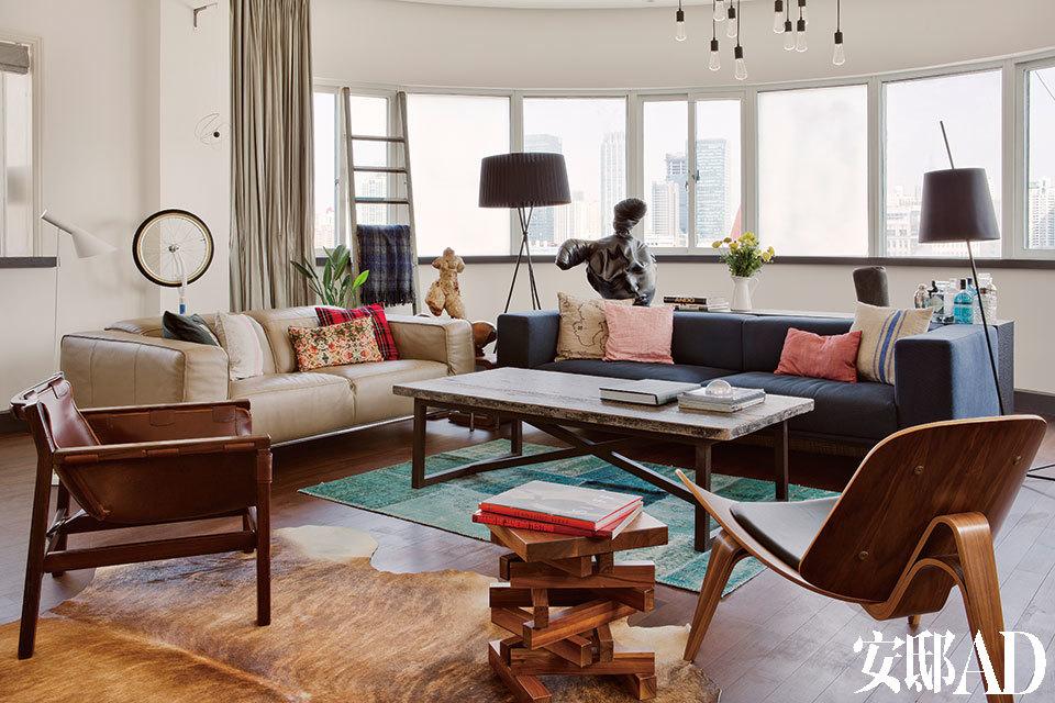 """来自约旦安曼的Lama和来自巴塞罗那的Ramon一年多前搬到上海。夫妇俩多年来的狂热收藏,为整个家带来生气,处处记录着他们旅居各地的浪漫轨迹。沙发后面条几上的铜质兔子头雕塑是Samuel Salcedo的作品,茶几旁边是上世纪50年代的古董皮质扶手椅,以及Hans J. Wegner著名的""""Shell Chair""""(三足贝壳椅),沙发是意大利米兰的家具制造商Flexiform的产品。"""