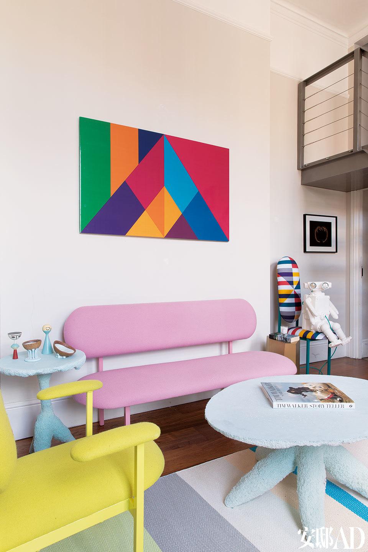 """你很难想象,这里过去曾是一间邋遢的公寓,主人用大胆的色彩与定制设计将它彻底改头换面了。客厅沙发上方的画作是一幅绘制在木板上的丙烯画,来自设计师David David。沙发和椅子来自Nina Tolstrup的作品集""""Re-imagined""""。桌子来自""""Cotton Candy""""作品集,由荷兰工作室Handmade Industrials制作,浇注聚氨酯制成。地毯来自丹麦品牌HAY,由Scholten &Baijings设计,100%纸制。白色机器人陶瓷灯具由Matias Liimatainen设计,在Peridis的画廊有售。右侧画作是Stephen Morallee 的影印作品,来自他的开普敦系列。"""
