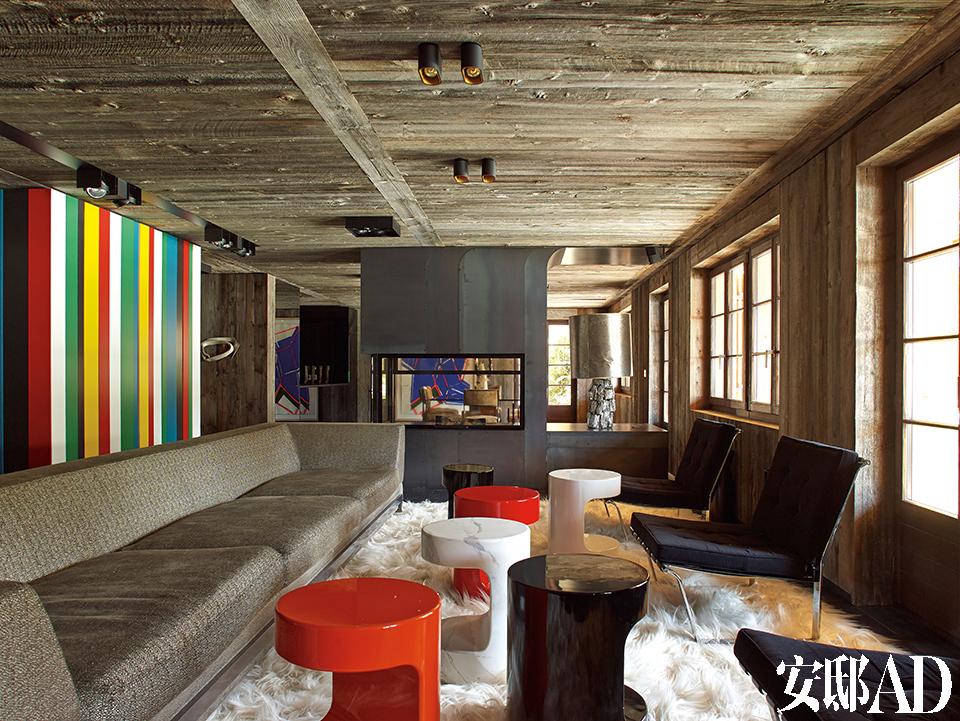 房屋一侧采光,雪山的强光照射进来,反差很大。天花板上可调光的射灯全天候调节光线,从而弥补了这一缺陷。客厅中超大尺寸的沙发和红黑白三色的漆面茶几(也可用作矮凳)都出自Thierry Lemaire之手,远处壁炉台上的云母矿物灯来自Gallery Yves Gastou。