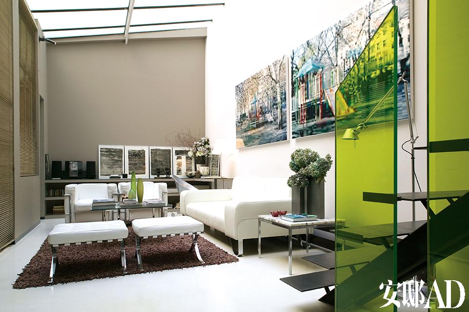 半透明天窗给客厅带来了充足光源,墙面的灰白对比则优化了光线。白色真皮沙发为Poltrona Frau品牌,两把扶手椅则是Le Corbusier设计的LC2,对面是两把由Mies van der Rohe设计的白色巴塞罗那椅脚凳,来自Cassina。母鹿皮地毯为Toulemonde Bochart品牌,墙上的两幅摄影作品出自Olaf Rauch之手。一旁的Tolomeo Terra落地灯来自Artemide。