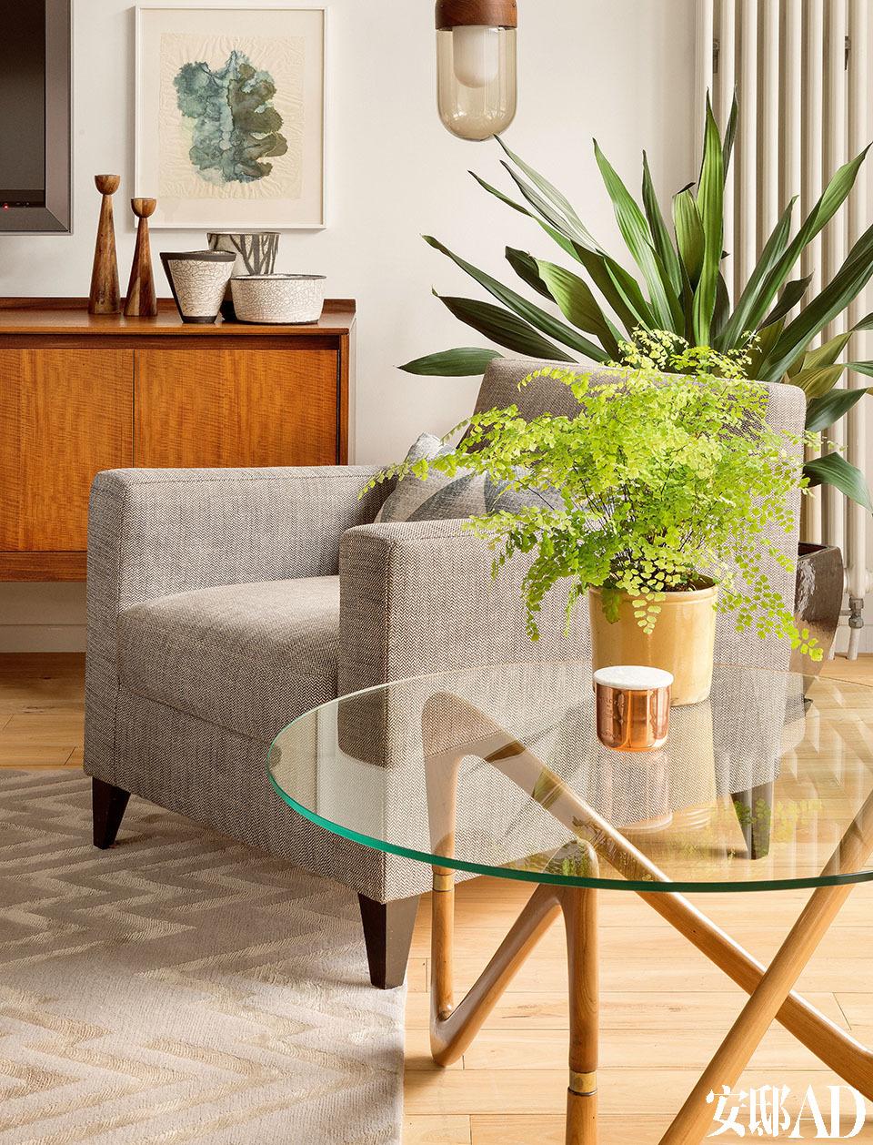 """""""女主人身上时常流淌着善意与平和的能量,她知性又热爱艺术,品位卓然又理解设计,最重要的是还非常开放。我们在打造这个家时,一直想着这样一个完美的形象。"""" ——设计师Lisa和Niki客厅的细节,近处的圆形玻璃茶几来自复古产品店Henry Saywell,单人扶手沙发均由Ligne Roset出品,地毯购自The Rug Company,玻璃吊 灯为Walnut Bell Pendant,来自伦敦一家专门经营人工吹制玻璃的品牌Heal's。后方电视机柜上的陶瓷摆设来自Malcolm Turner,绿色水彩画由Gavin Richardson创作。"""