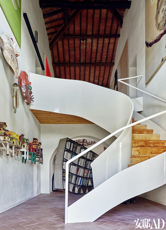 """楼梯由MdAA建筑工作室设计。左侧墙壁上的艺术作品被分成三行挂设,这加强了家里这部分空间的双重高度感。从下往上,最近的是 中国艺术家陈箴2000年用蜡烛制作的作品Un Village sans frontières; 第二行是Luigi Ontani (1998/2009)的作品Máscaras Musicales《音乐面具》,第三行的绿色图画Whiring Green是意大 利艺术家Aldo Mondino 1997年的作品。楼梯右侧的墙壁上挂着Julian Schnabel的画作。照片 的尽头,楼梯的后方是Ron Arad在2007年设计的书架""""Restless""""。"""