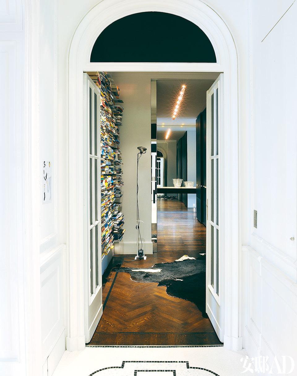 黑白小格的地板,20世纪早期风格的门和黑色玻璃,这一切让门廊显得惊艳极了。书架是Luca本人的设计。落地灯名为Toio,是Archille Castiglione为Flos设计的产品。