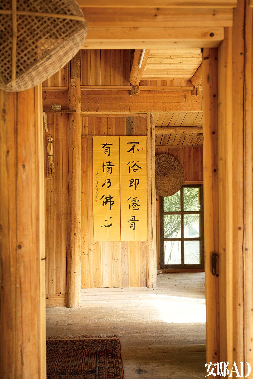 室内的地板、墙面大多由当地盛产的杉木打造,和暖的木色更鲜亮地衬托出窗外的青瓦修竹。一位佛家禅师在这里居住之后,留下了这副对联,李见深觉得他的字清新而不带火气,便挂在木质墙面上。