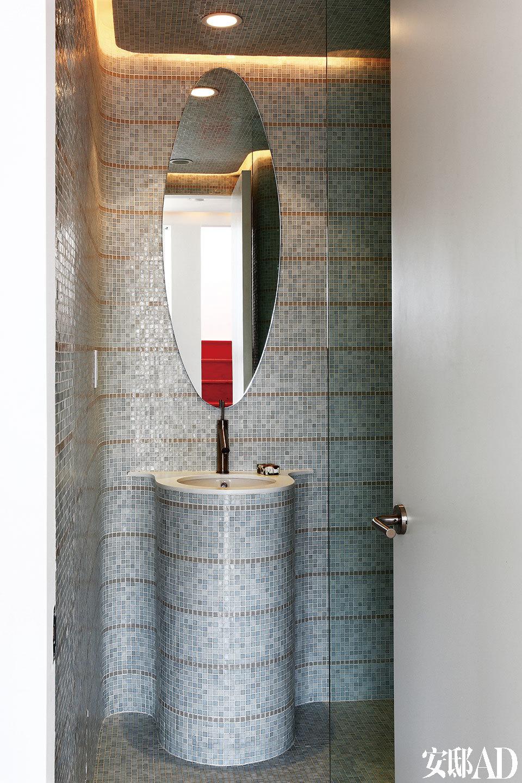一间设计独特的浴室中,马赛克瓷砖来自Bisazza,水龙头由Philippe Starck设计,Axor出品。椭圆形化妆镜由Cecilia设计,大理石面的洗脸池侧面也装饰了马赛克,与墙面融为一体。