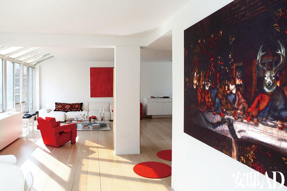 整面落地窗为红调客厅带来明媚阳光,有些古典味道的画作,为整个空间作了恰当的平衡。客厅中,18世纪的古董座椅和现代设计的白色沙发形成鲜明对比。Felt Utrecht扶手椅是Gerrit Rietveld为Cassina做的设计,搭配了同样来自该品牌由Piero Lissoni设计的玻璃面茶几。鲜艳的红色家具及饰品,比如红色圆毯、扶手椅和挂画,成为了当仁不让的装饰亮点。近处的画作《Animal Last Supper》出自Lydia Venieri之手。