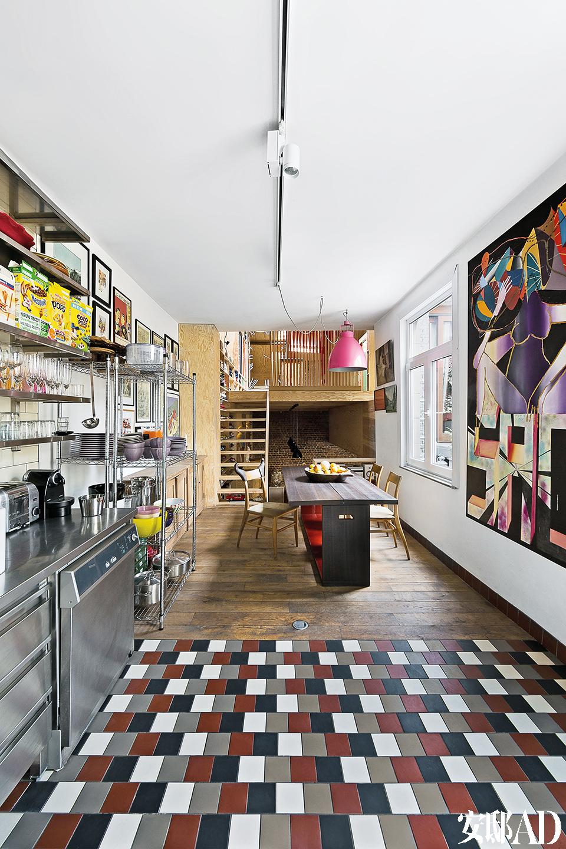 紧挨着厨房的餐厅里有一张木质餐桌,来自加拿大Nor Sud品牌的餐椅设计得极富现代感。餐桌上挂着一盏粉色Jieldé大号吊灯,它成为了餐厅中最抢眼的物件。四色瓷砖地面,加之金属不锈钢搁架上琳琅满目的厨具, 令开阔的厨房显得酷感十足。
