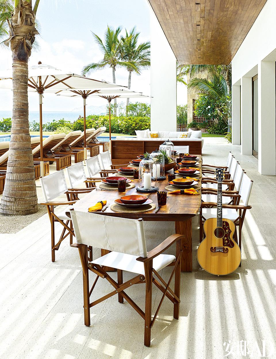 辛迪家的池边阳台常作为户外进餐的区域。定制餐桌旁放着Christian Liaigre折叠椅,Gibson吉他则是房子的常客KidRock赠送给夫妇二人的礼物。