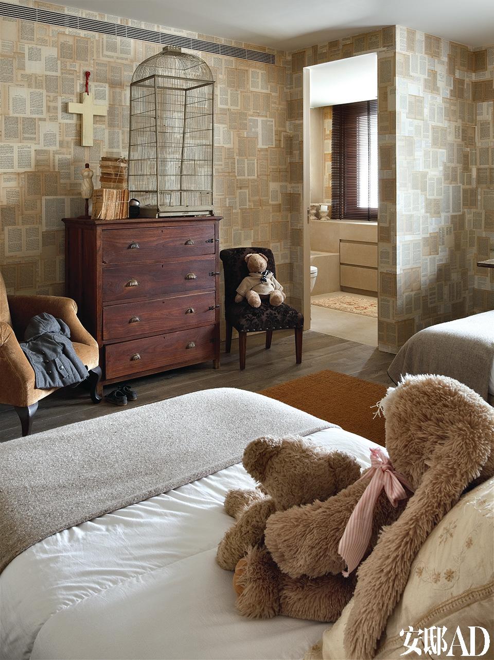 """儿童房里的自制壁纸成了家里的另一大亮点, 儿子的房间拼贴着航海图,两个女儿的房间则贴满了书页。女儿卧室里的""""书页""""墙很漂亮,墙边靠着19世纪的英国衣柜和鸟笼。"""