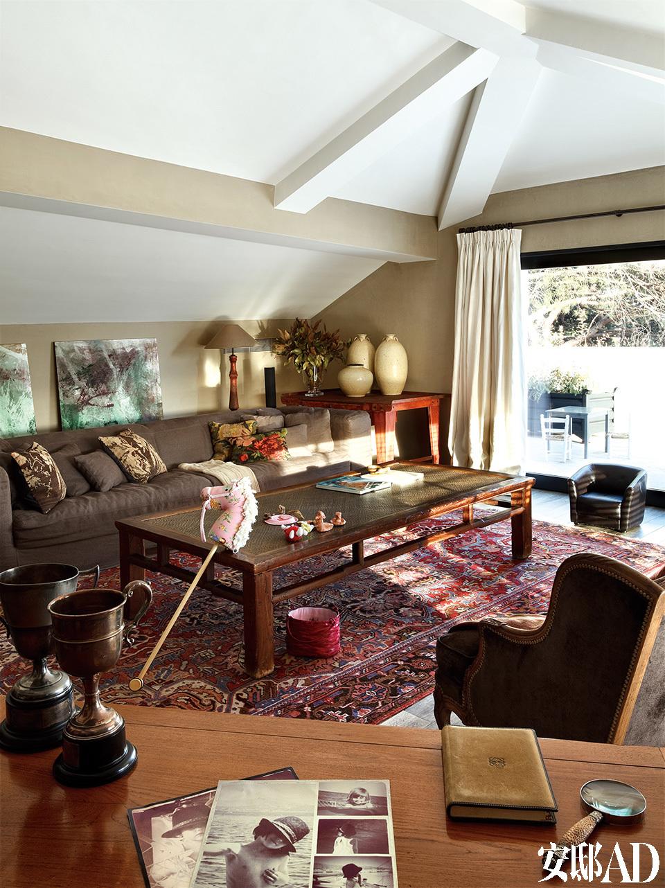 阁楼被改造成了孩子们的游戏房,沙发由Toni设计。后方也是Mariona Buxó的挂画,中式咖啡桌、伊朗地毯、法国扶手椅和桌上的奖杯均可在Azul Tierra购得。