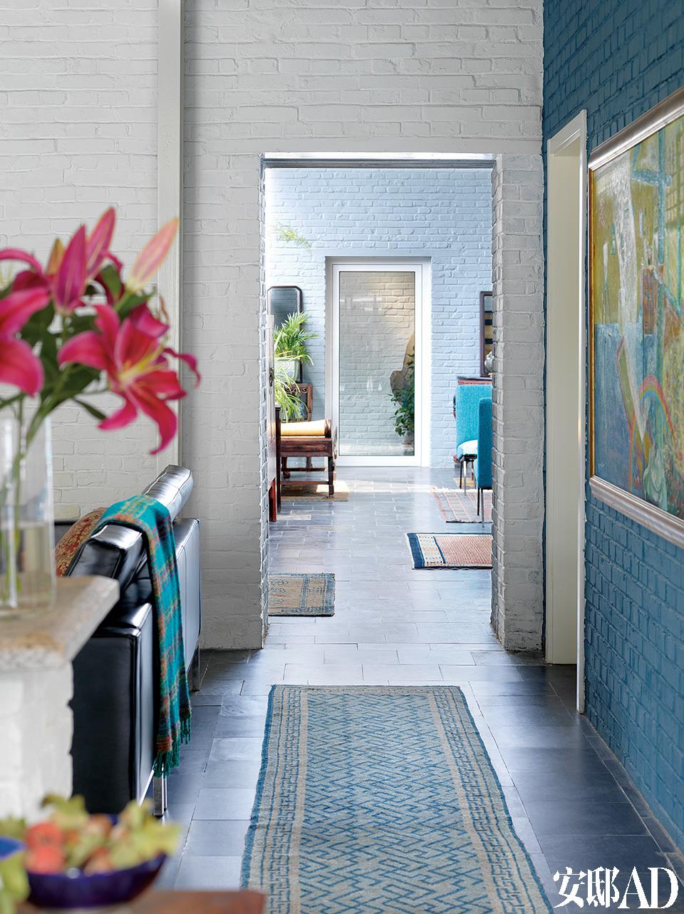 画面由近及远,旧起居室通往新起居室,尽头处一扇门连着后院,还能看到一块露出部分的原始山石,起居室里铺了从西藏等地买回来的地毯。