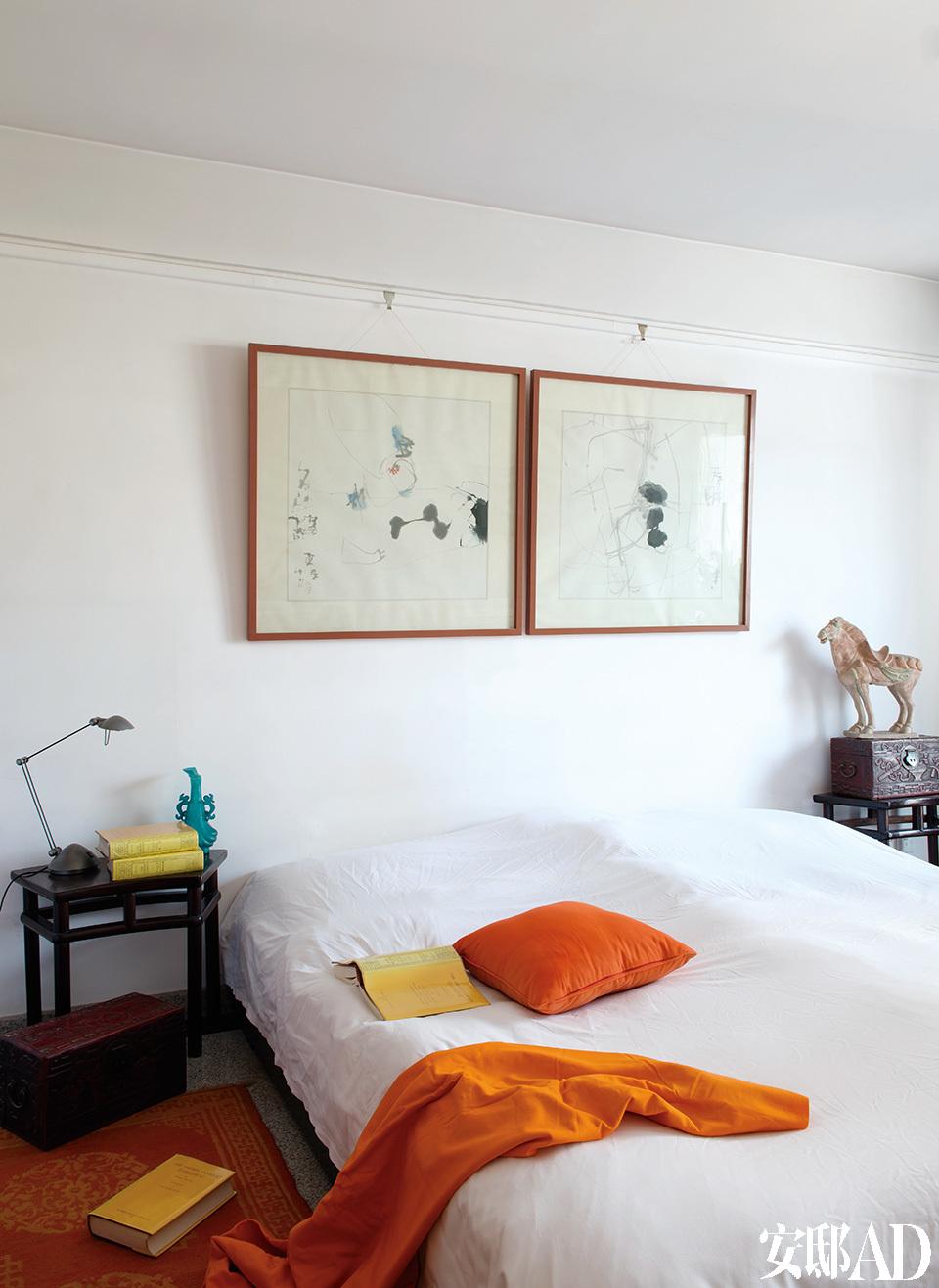 """另一间卧室中的墙上挂着两幅画家东泽的作品。他擅长以水墨手法画抽象的写意画,岳夫人很早就与他相识,在汉堡的家中也有他的不少作品。床两侧的小木桌是清代中期的家具,有趣的是它们各自有一定弧度,8个同样的木桌就可以拼成一个圆形。""""非常可惜我只买到了其中两个!""""岳夫人说。"""