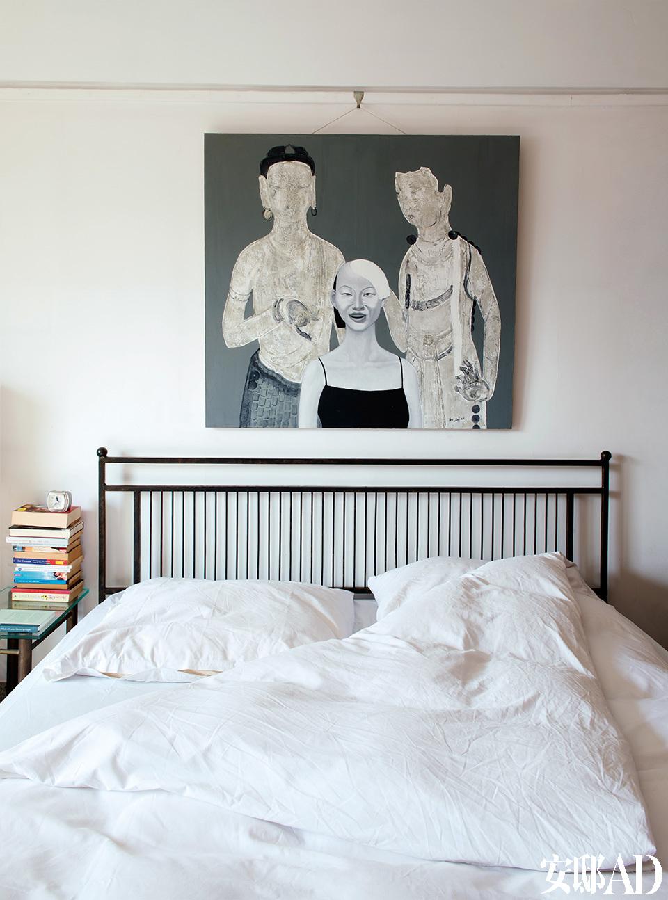 """主卧室中的油画来自肖红,岳夫人当时看到画中的三个人物,一下子就联想到了著名的""""宋氏三姐妹"""",于是便买下它。""""中间那位时髦的小姐就像我心中的宋美龄啊!""""岳夫人说道。铁质床以及旁边的铁质床头柜,都是由岳夫人自己设计,请铁艺家具制作师王志海打造的。肖红创作的油画,成了岳夫人心中的""""宋氏三姐妹"""",与她自己设计的复古铁床在色调上完美契合。"""