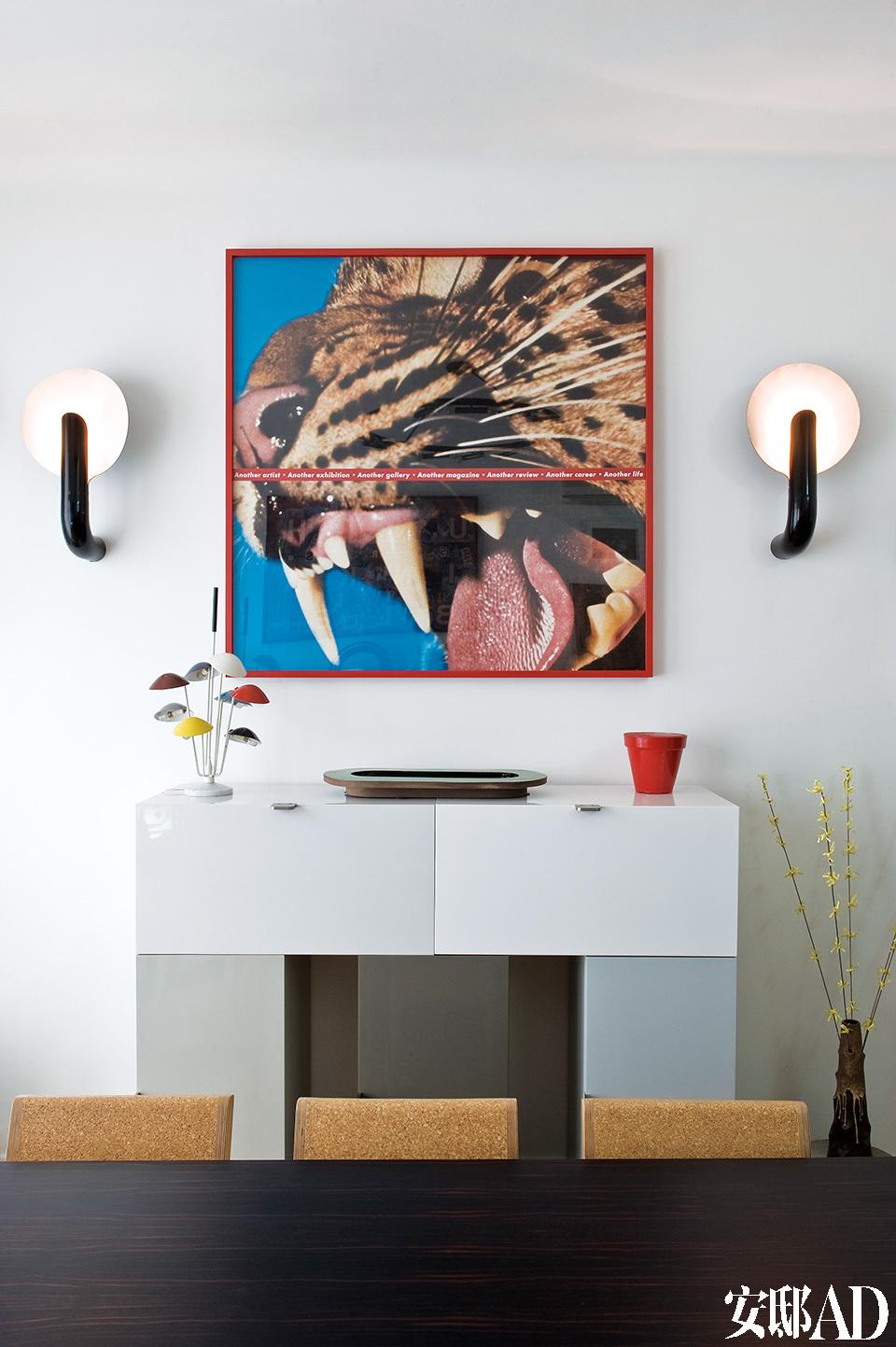 """餐厅中挂着Barbara Kruger拍摄的照片,两旁的Elysée壁灯由Pierre Paulin设计。画下的餐具柜名为""""巨石阵""""(Stonehenge),设计者是Françis Bauchet,台灯是Gino Sarfatti的作品,中央摆放的瓷盘由Pierre Charpin设计,餐桌椅出自Martin Szekely之手。"""