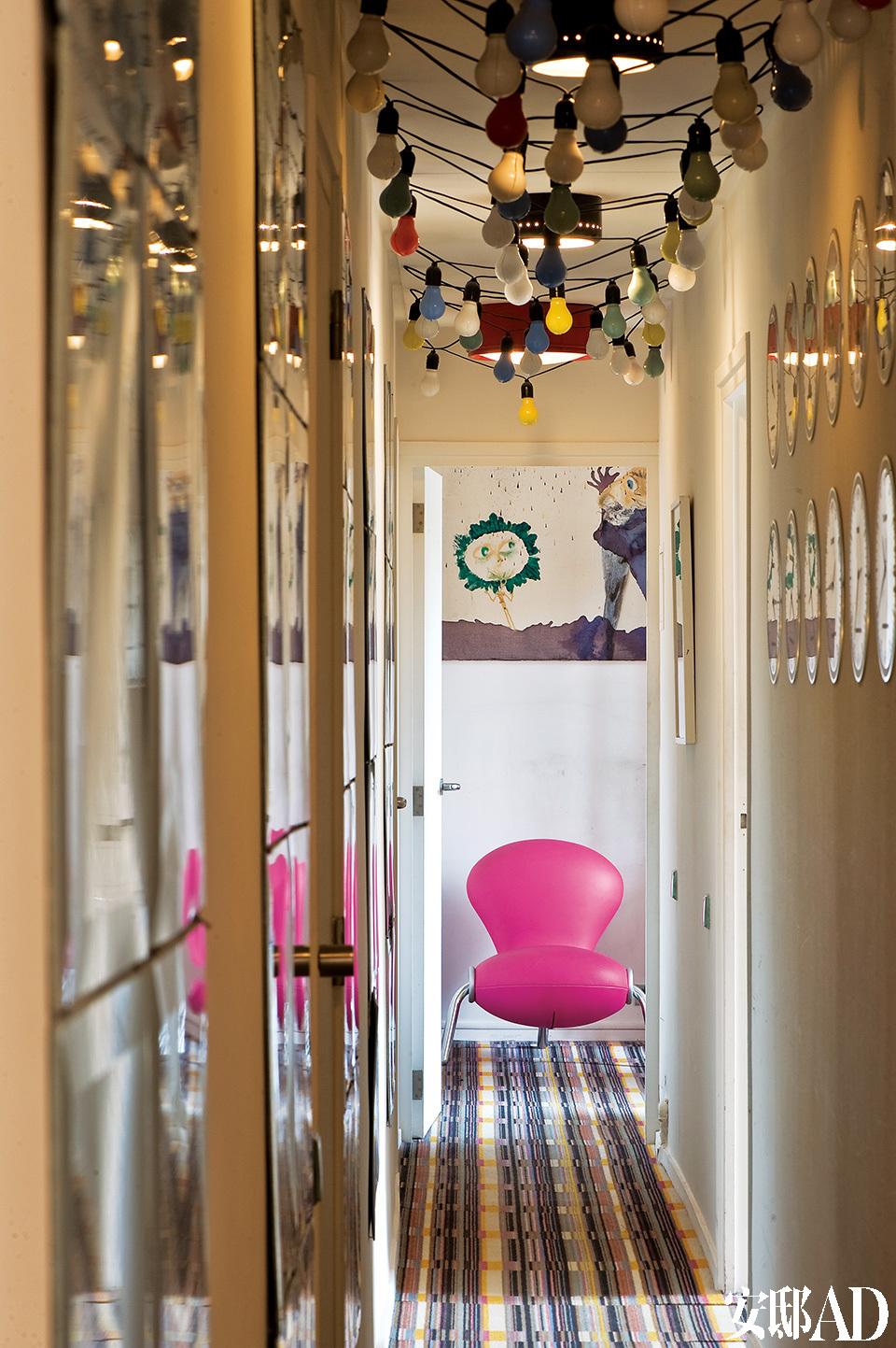 """从走进家门的第一刻起,各种艺术、设计品就扑面而来,令你眼花缭乱。走廊中,天花板装饰的设计者是Etienne Bossut,地毯来自Bouroullec兄弟,粉色椅子""""Embryo""""是Marc Newson的作品。"""