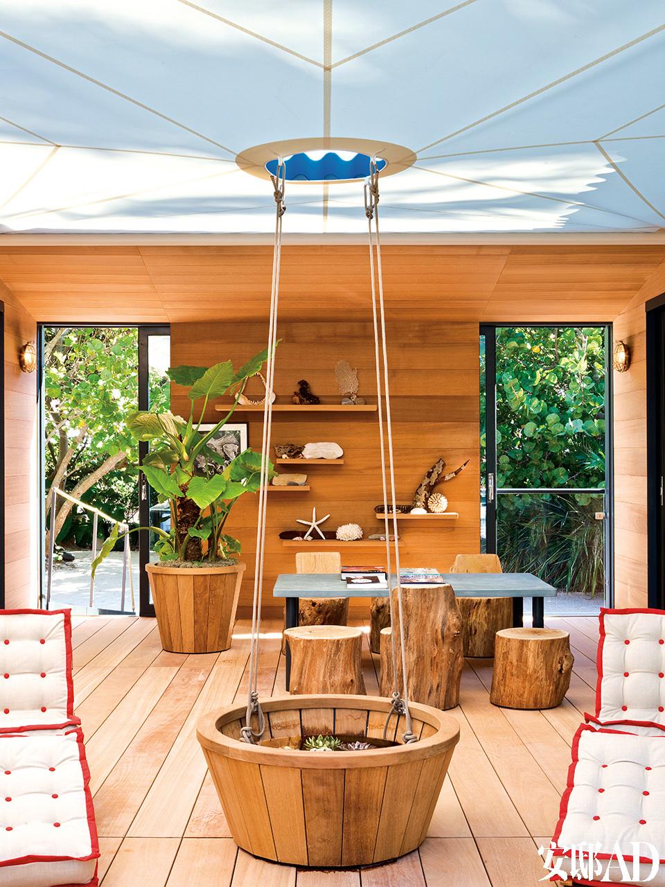 """独特的设计让人仿佛置身于船上,一张简单的船帆在屋顶撑开,使得这间露天房屋免受阳光直射。在前排,两把覆盖有红色镶边坐垫的长椅吸引着人们的眼球,长椅源自夏洛特在1929~1942年期间创作的家具系列,这一系列家具是根据档案图片专为""""水上之屋""""项目定制的。"""
