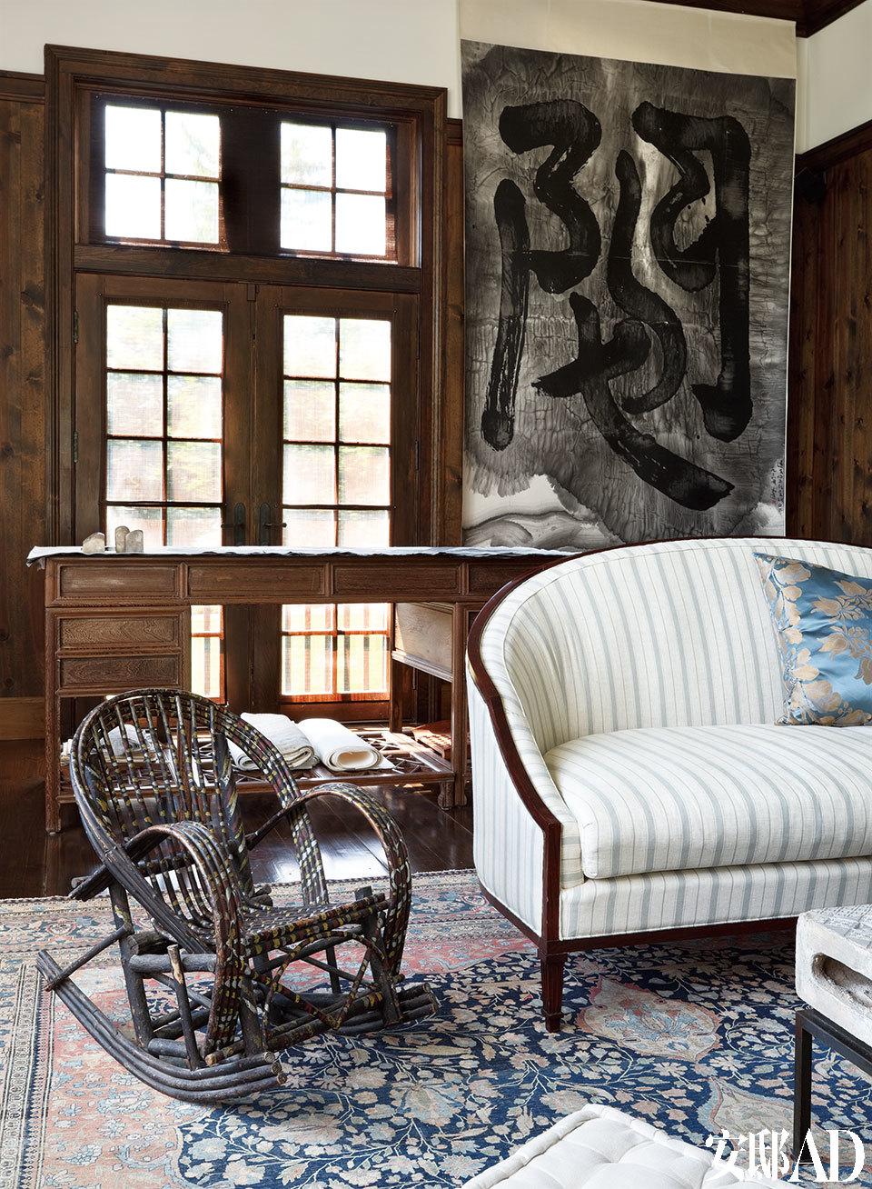一把来自老上海的藤条儿童摇椅带给客厅很多温情,其线条和质感竟与墙上的书法和地上磨旧的地毯如此相互呼应。