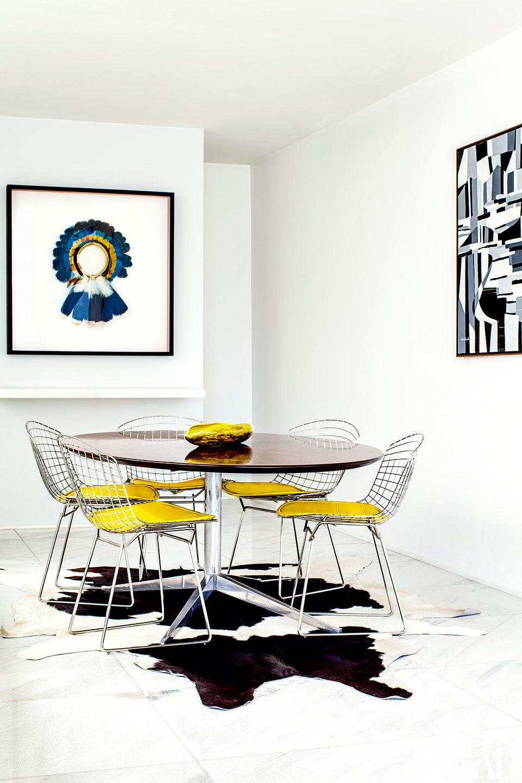 墙面几乎纯白,地面则是略带条纹的 大理石,这使得整个家的光线极为有个性。餐厅里,餐椅来自Bertoia,餐桌来自Florence Knoll,花瓶来自Saint-Clement,地上是奶牛皮质的地毯。墙上挂着的羽毛头饰艺术品来自亚马孙地区的原始部落,另一面墙上挂着巴西艺术家 Claudio Faciolli的画作。
