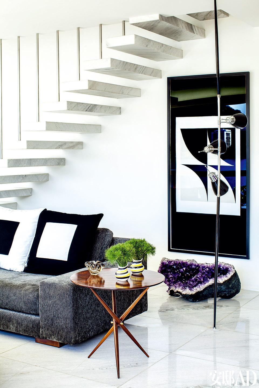 这是一幢上世纪60年代建成的复式别墅,清新的热带绿植主宰着整个空间的气质。复古沙发和复古立灯搭配Sergio Rodrigues设计的紫檀木小圆桌,许多中国人用以调整风水的紫水晶洞,在这个家中都是以艺术品的姿态出现的。沙发后的墙面上悬挂着 Arcangelo Ianelli的作品。