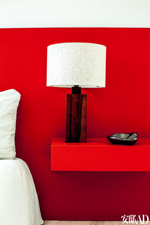 Sergio Rodrigues设计的台灯放在特制的红色漆质床头前,特别显眼。