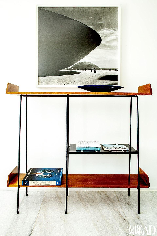 主卧里摆放着两用的置物架书桌。墙上的摄影作品来自Marcel Gautherot,摄于上世纪50年代,图上的内容为巴西利亚的一幢建筑物。