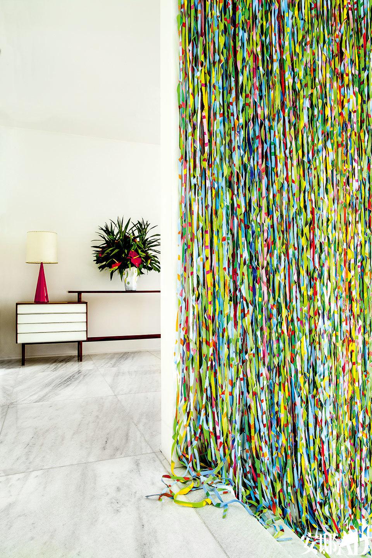 """我在这里诠释了自己对时尚的认知:意料之外的细节融汇交织出一派简约风格。""""客卧入口处的垂帘也是一件艺术品,名为《Floresta Tropical》,来自艺术家Lauro Muller。瓷质台灯和小柜来自Roberto Allano,均为上世纪50年代末的家居艺术品。"""