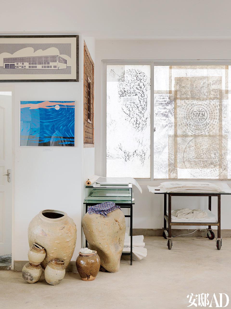 这个家从建筑到室内设计,都是由韩湘宁亲自操刀,有一种挑战常规的艺术家浪漫情怀。二楼一角,墙面上是波普大家Roy Lichtenstein的版画(上)和原作(下),罐子里装着纸和画,窗户上贴着韩湘宁的画作。