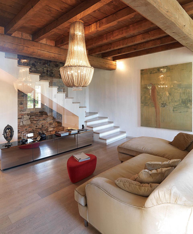 楼梯后一整面裸露的原始砖墙,就像一幅画,讲述着老建筑的历史。客厅的另一侧,一组Keu小桌上展示了几件来自Wunderkammer Visionnaire的摆件,其中包括Rita Miranda的乐烧陶器、Alessandro Brighetti的雕塑作品《Cuore》、由Domenico Grenci创作的肖像画,以及Vanessa陶瓷蝴蝶。墙上的画作出自Emmanuel Barcilon之手。