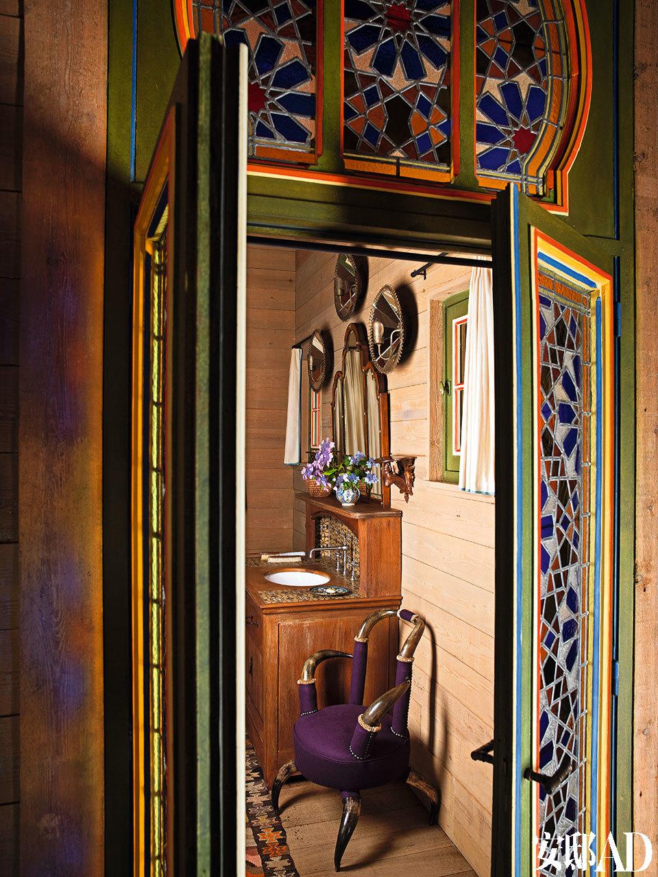 打开着色玻璃门后是卫生间;古董法式梳妆台上挂着几盏19世纪的壁灯,扶手椅也是19世纪的奥地利制造的。