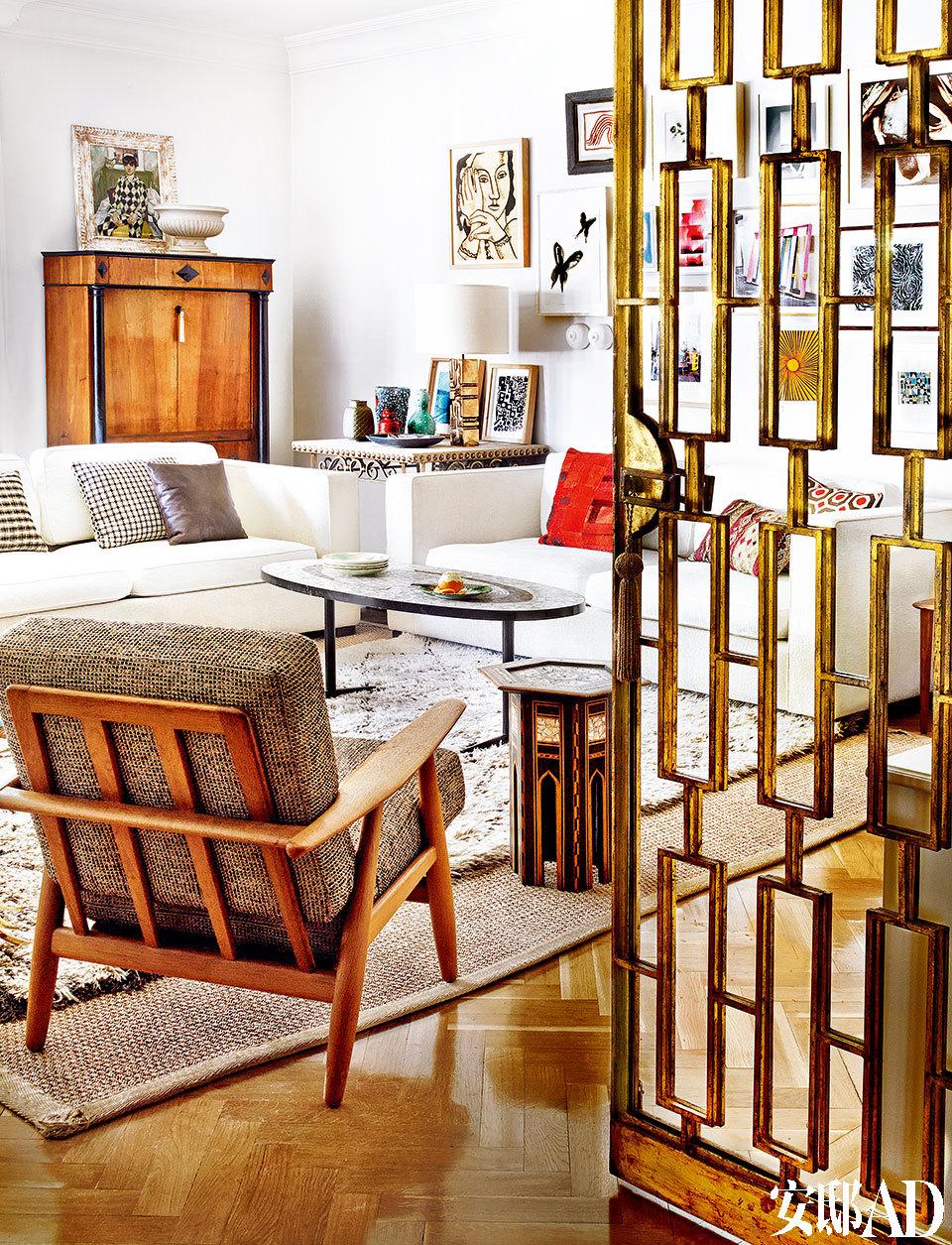 """客厅另一角。Nobilis花呢面扶手椅是在Mfaktum购买的,摩洛哥小边桌来自丹吉尔。远处是一个家传的19世纪文件柜,上面摆着Montse的母 亲画的小丑油画。剑麻席上铺着在Siesta Y Mant A购买的Beni Ouarain羊毛地毯。""""我为了这个房子里那些包金的格栅而买下了'她',而且当时'的她'足够破旧,给了我随意改造的自由!"""""""