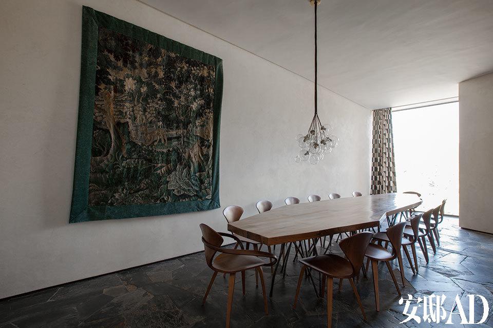 """餐厅的地面上铺着不规则形状的深色板岩,多足餐桌""""Mille Pattes""""由Ko设计工作室为这个家定制而成,主人在这里可以同时接待20位宾客。胡桃木餐椅来自19世纪中期最具代表性的美国家具设计师 Norman Cherner,吊灯的玻璃外罩出自玻璃吹制工Myriam Roland-Gosselin之手,Kubus亚麻窗帘来自法国Pierre Frey品牌。地面由不规则形状的深灰色石材 拼接而成,逆光下尤其呈现出朴实无华的润泽质感。"""