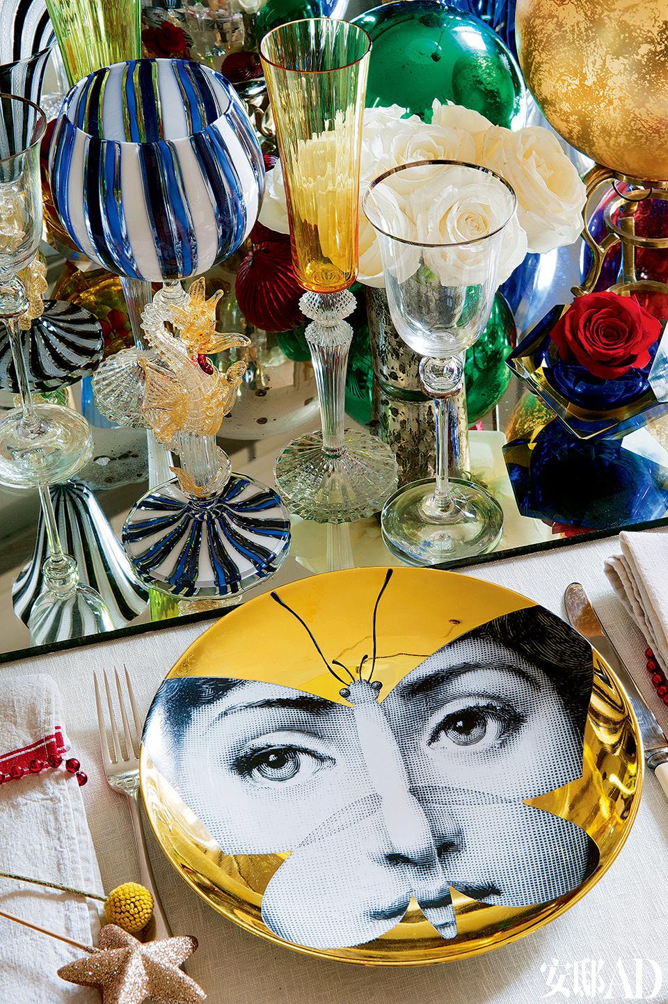 圣诞餐桌的细节:Fornasetti的盘子是整个家灵感魔力的来源,Gambara的银制英式餐具和摆放在镜子上的来自Murano的Baccarat酒杯则彰显着主人的生活品质。