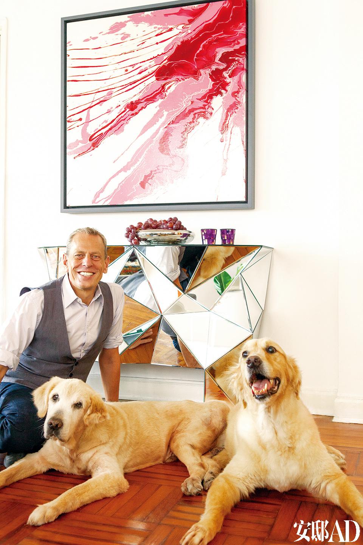 艺术家Gerry Bookle和他两条忠诚的金毛,他的背后是Tequila Kola出品的几何镜面条案,上方挂着他自己的画作。