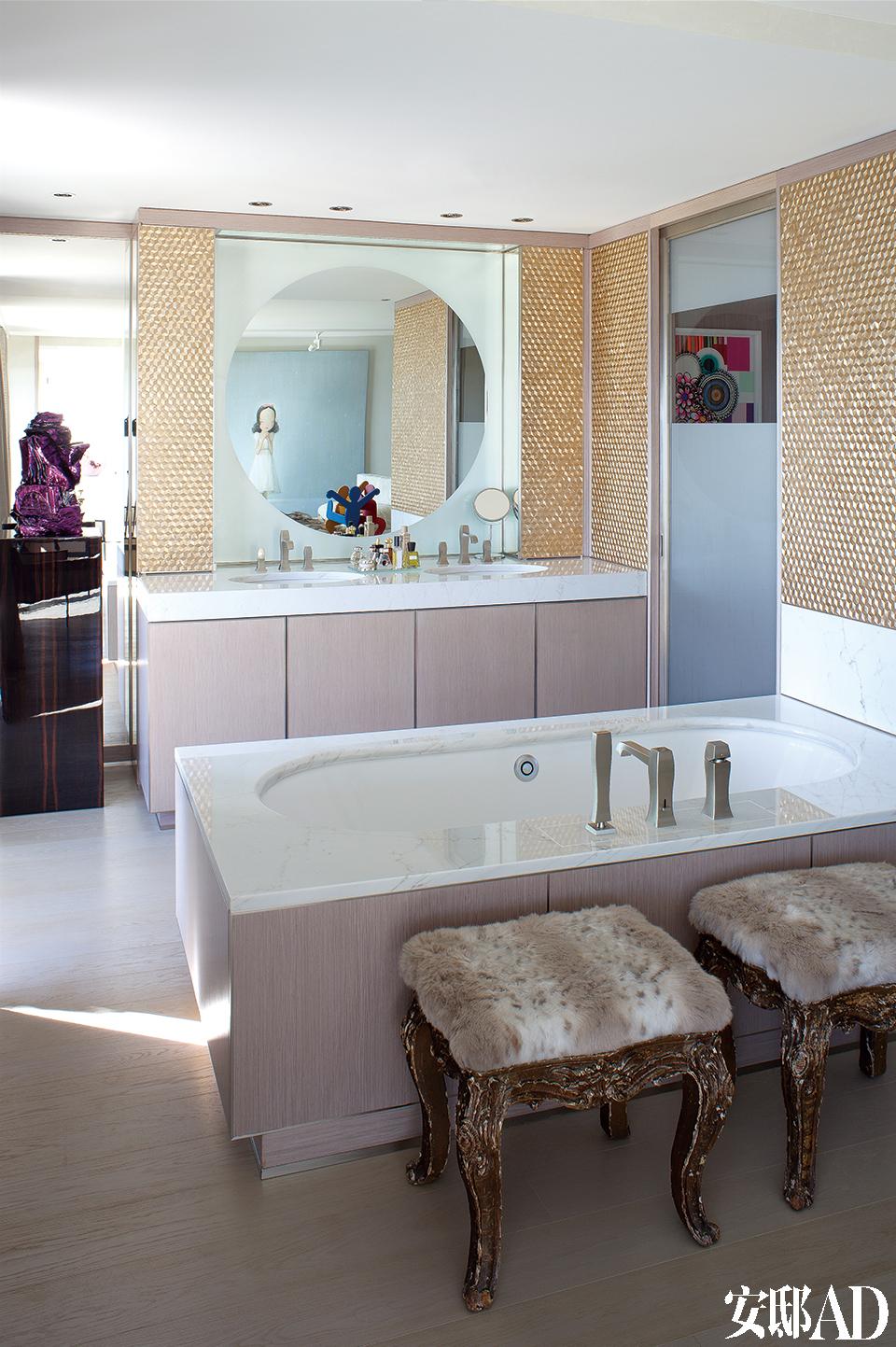 浴室里,Kaldewei浴缸,Gessi水龙头,两个盖满皮毛的Napoléon III墩状软座来自Fabienne的祖母家。墙上覆盖着粉红色金属镶嵌瓷砖。左边可以看见一个出自Anselm Reyle的淡紫色系雕塑,在盥洗盆上方的镜子里面是中国艺术家刘野的作品,在右边的镜子里面,我们依稀能够看见Beatriz Milhazes的作品。