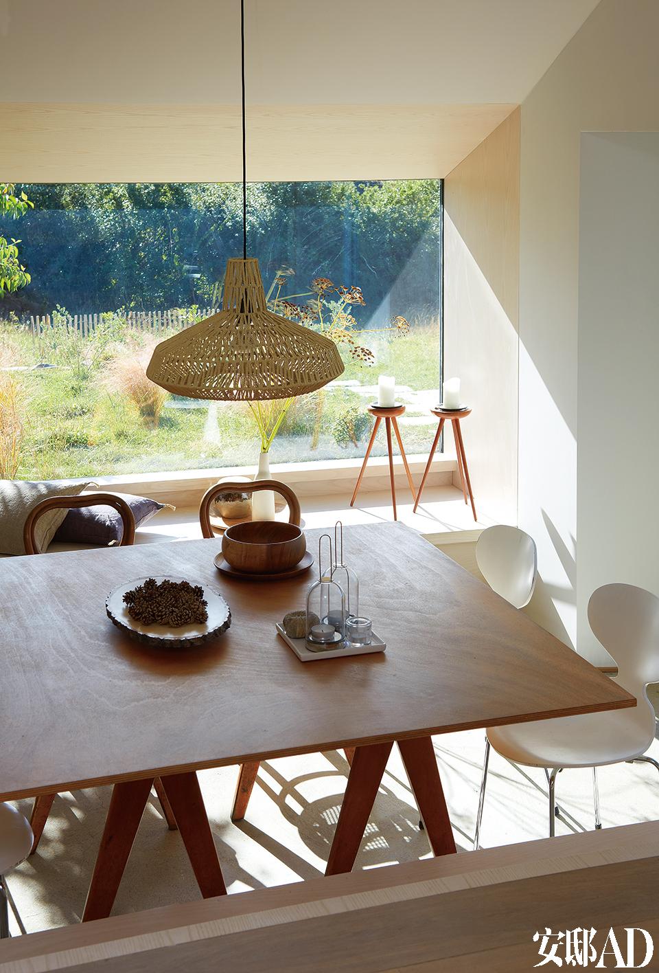 大面积玻璃窗让老屋顿时透亮了许多,宽大的浅色窗台更像是为户外美景定制而成的画框。餐厅的地面采用了裸露的混凝土材质,餐桌由拍卖会买到的老支架和一张简单的胶合板组成,桌上是斯堪的纳维亚风格的木盘,蜡烛台来自Eva Solo。Arne Jacobsen 设计的Ant椅(Fritz Hansen出品)和风行150多年的Thonet椅组成了餐椅,编织吊灯来自Habitat。