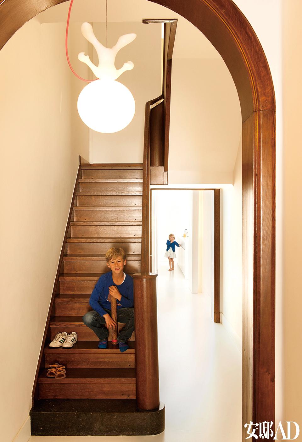 新装的楼梯采用了木质材料,与各个房间里的木地板相呼应,带来温暖的质感。坐在楼梯上的,是Kris夫妇俩8岁的儿子Edgar,远处厨房里的小女孩儿, 则是比Edgar小两岁的妹妹Julia。