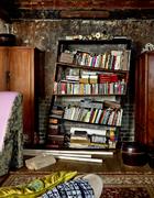 """倚着乌青墙的一例书架歪歪斜斜, 气质异于常 人的冰逸笑称自己""""就喜欢颠三倒四""""。大厅西侧房间兼有卧房和起居室之用,倚着乌青墙的一例书架歪歪斜斜,众沙发中立着一个形如高跟鞋的紫面花帮沙发,由冰逸自己设计。"""