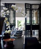 """餐厅以深沉的木色为主,餐桌在中国定制,可容纳20人同时就餐,满足主人的宴请需求。Marie France用好友Elad Yfrach为L'Objet设计的产品搭配着Raynaud白色古董瓷器餐盘。餐具来自Christofle,玻璃制品中既有来自Baccarat的高端设计,又有""""看起来很棒,摔起来也不心疼的""""平价产品。"""