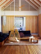房内放置了多个内置的沙发和座椅,上有靛青色亚麻靠垫。低矮的咖啡桌选材是当地的硬木,低调又不失功能性。吊篮椅是为这座别墅度身定制的,显出趣意盎然的氛围。悬挂的贝壳风铃已改装成灯具,宛如大海中游弋的水母。