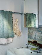 卫生间以青色为主基调,棉麻质地的毛巾、灯塔版画和淡绿色的肥皂让简约的角落更精致清爽。