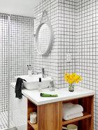 浴室位于卧室与客厅之间,呈长条状。只用最简单的10cm x 10cm的白色瓷砖贴满四面,却显得简洁爽利,颇有极简风姿。墙上的镜子来自Vitra,是HAY Studio在2003年推出的作品。