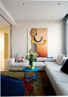 与客厅和书房相比,生活区的用色更加恬淡,营造出温馨的居住氛围。卧室区的小客厅附带电视,主要用于家人休闲娱乐。沙发和蓝色茶几来自丰意德,地毯是毯言织造出品的MF-5033,茶几上的镀金雕花瓷碗L'Objet购自Lane Crawford连卡佛,墙上的画由加藤泉创作。