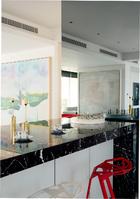 西式厨房向客厅开放,黑色大理石岛台上的两只金色烛台为La Mont,来自家天地。岛台一侧的镜面墙内暗含一个电视屏幕,岛台周围的两排红白色Konstantin Grcic吧凳来自Magis品牌。