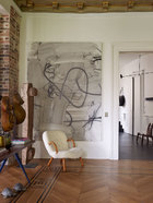 墙上的艺术品来自Christopher Wool,一把山毛榉制成的Clam安乐椅由Philip Arctander设计于1944年,Nordisk Staal & Møbel Central在1940年代晚期出品。背景是入口处,原有的镶木地板经过了修复。