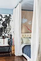 """喜欢宽敞空间感的沈伟将原本的隔间打掉,以亚麻布帘作为卧床和客厅的空间区隔。卧床墙上是以亚麻布为底的画作,沈伟当年装潢时每天一点一点地创作,""""觉得这抹红白很适合这个卧床,很安静清新的感觉。"""""""
