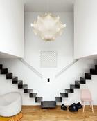 """正厅中,在充当卧室的两个悬空""""箱子""""中间,天花板以下的空间被预留出来。出自Achille和Pier Giacomo Castiglioni的""""Taraxacum S """"复古吊灯在那里熠熠生辉。地面上是A+A Cooren的""""Orbit""""灯具(来自Ymer & Malta工作室)和David Geckeler 设计的""""Nerd""""椅子(Muuto au Bon Marché)。墙上则挂着Marc Cavell的作品《Building》(来自88画廊)。"""