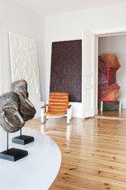 """"""" 在我的家里,每个房间都是一个简单的白色立方体, 它们相连在一起,就仿佛一座特别的个人收藏馆。""""靠墙的一黑一白两幅画作名为《And,Une》,出自Guillaume Leblon之手,一旁的金属架皮革扶手椅由Ilmari Lappalainen设计,近处的桌面上摆设着几只非洲部落风的头像雕塑,来自瑞士年轻艺术家Flurin Bisig。"""