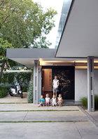 Danica带着4个孩子站在她家门前。前门可以无缝地收入墙内,为房子里的艺术收藏奠定了基调。门本身就是一件功能卓越的艺术品,由约翰内斯堡的艺术家Marcus Neustetter基于Google Earth中约翰内斯堡的图像创作而成。